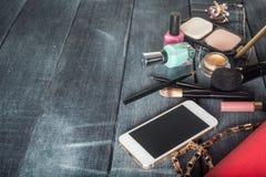 Bolsa fêmea com cosméticos e móbil no fundo das calças de brim foto de stock