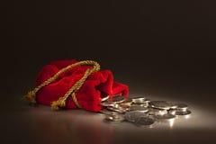Bolsa roja con las monedas Foto de archivo