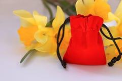 Bolsa roja del terciopelo con las flores amarillas en un fondo blanco fotografía de archivo libre de regalías
