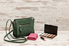 Bolsa verde pequena das senhoras, bolsa cor-de-rosa, paleta da sombra e batom no fundo de madeira Conceito da forma Imagens de Stock Royalty Free