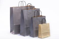 Bolsas de papel grises y marrones con las manijas para hacer compras Imagen de archivo