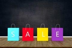 Bolsas de papel de las compras para la publicidad de la venta en la tabla de madera con el blac fotos de archivo