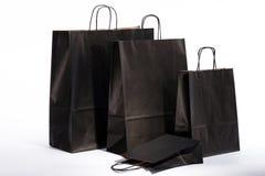 Bolsas de papel negras con las manijas para hacer compras Foto de archivo libre de regalías