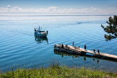 Bolshiye Koti,俄罗斯- 7月18 :macrophototour,队的队员等待小船并且在贝加尔湖附近拍照片 免版税库存图片