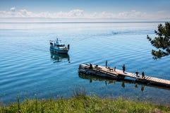 Bolshiye Koti, RYSSLAND - JULI 18: macrophototour medlemmar av laget väntar fartyget och tar bilder nära Lake Baikal Royaltyfri Bild