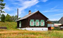 BOLSHIYE KOTY, IRKUTSK-REGION, RUSSLAND - 24. Juli 2017: Hölzerne russische Hütte mit grünen Fensterläden auf Fenstern Lizenzfreie Stockfotos