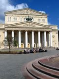 Bolshoi theater in Moscow. People rest on the benches on the square. Stock Photos