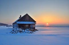 Bolshoy Kadilniy,俄罗斯, 2017年3月, 06日 Bolshoy Kadilniy海角的木房子在贝加尔湖岸的日出  库存照片