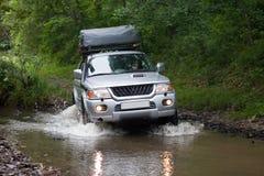 BOLSHOY KAMEN, RUSSIE - 3 AOÛT 2015 : SUV traverse une rivière Image libre de droits