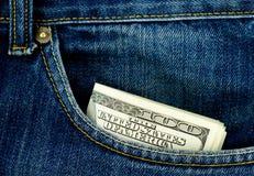 Bolsillo de los pantalones vaqueros con cientos dólares de billetes de banco Imágenes de archivo libres de regalías
