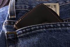 Bolsillo de los pantalones vaqueros con efectivo fotos de archivo