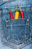 Bolsillo de vaqueros proveído de personal con las pimientas frías rojas y amarillas, fondo del dril de algodón Pimientas en el bo Imagen de archivo