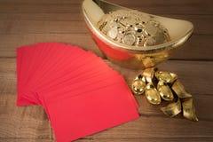 Bolsillo rojo y lingotes de oro chinos antiguos en de madera Imagen de archivo libre de regalías