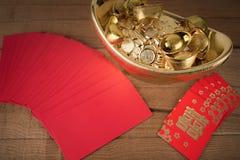 Bolsillo rojo y lingotes de oro chinos antiguos en de madera Imagen de archivo