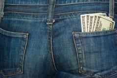 Bolsillo trasero de los pantalones vaqueros con $100 billetes de banco Foto de archivo libre de regalías
