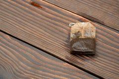 Bolsita de té usada en fondo de madera Imagen de archivo