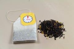 Bolsita de té y hojas de té negras Imagen de archivo libre de regalías