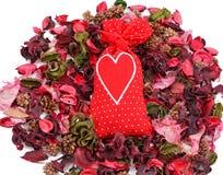 Bolsita roja con un corazón en el fondo de pétalos Imágenes de archivo libres de regalías