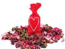 Bolsita roja con un corazón en el fondo de pétalos Imagenes de archivo