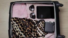 Bolso abierto del ` s de la mujer en una mesa con ropa y accesorios, ella es que embala y que consigue lista para irse, para viaj metrajes