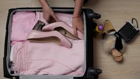 Bolso abierto del ` s de la mujer en una mesa con ropa y accesorios, ella es que embala y que consigue lista para irse, para viaj almacen de metraje de vídeo
