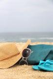 Bolso azul de la playa en el sombrero de la costa y de paja Fotos de archivo libres de regalías