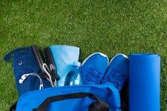 Bolso azul en la hierba verde, con un sistema de cosas y zapatos de los deportes, agua en la botella y música para el humor Foto de archivo