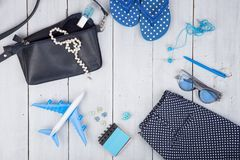 bolso azul, gafas de sol, chancletas, esmalte de uñas, cuaderno de notas del auricular y poco aeroplano en el fondo de madera bla Imagenes de archivo