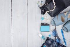 bolso azul, gafas de sol, sandalias, esmalte de uñas, cuaderno de notas del auricular y poco aeroplano en el fondo de madera blan Imagen de archivo