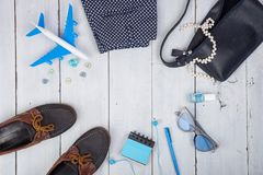 bolso azul, gafas de sol, zapatos, esmalte de uñas, cuaderno de notas del auricular y poco aeroplano en el fondo de madera blanco Imagen de archivo
