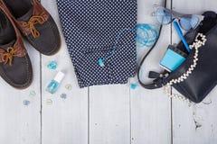 bolso azul, gafas de sol, zapatos, esmalte de uñas, cuaderno de notas en el fondo de madera blanco Imagen de archivo libre de regalías