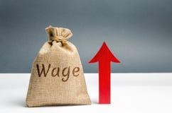 Bolso con el dinero y salario y para arriba flecha de la palabra Aumento del sueldo Tarifas salariales Crecimiento de la carrera  fotografía de archivo