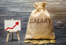 Bolso con el dinero y el sueldo de la palabra y encima de la flecha y de monedas Aumento del sueldo, tarifas salariales promoción imagenes de archivo