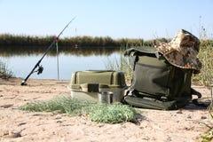 Bolso con la pesca de esencial en la orilla fotografía de archivo