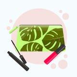 Bolso cosmético con un modelo de hojas tropicales Bolso cosmético con las herramientas para el maquillaje profesional: lápiz labi Fotografía de archivo