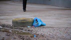 Bolso de basura azul del primer con las mentiras inútiles al lado del charco del neumático del suciedad y de goma de la rueda cer almacen de metraje de vídeo