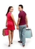 Bolso de compras de los pares que lleva felices atractivos Fotografía de archivo libre de regalías