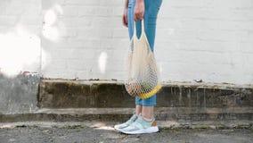 Bolso de compras hecho punto secuencia reutilizable de la malla de las piernas de la muchacha con las frutas y verduras, moviéndo almacen de metraje de vídeo