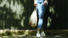 Bolso de compras hecho punto secuencia reutilizable de la malla de las piernas de la muchacha con las frutas y verduras, moviéndo almacen de video