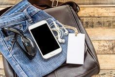 Bolso de cuero de Brown, mezclilla azul, teléfono elegante y auricular en t de madera Fotos de archivo libres de regalías