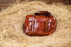 Bolso de cuero en el heno Imágenes de archivo libres de regalías