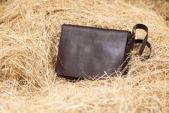Bolso de cuero en heno Imagen de archivo libre de regalías
