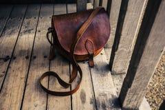 Bolso de cuero en terraza de madera Imágenes de archivo libres de regalías
