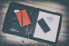 bolso de cuero oscuro para los documentos en él la inscripción del plan de la palabra Hay una pluma, un teléfono, una guirnalda y fotografía de archivo libre de regalías