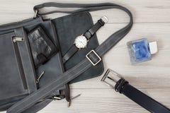 Bolso de cuero para los hombres con la cartera y el reloj en fondo gris imagen de archivo libre de regalías