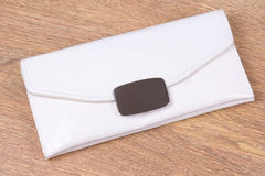 Bolso de embrague blanco con en el fondo de madera Imagen de archivo libre de regalías