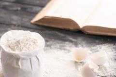 Bolso de la harina y de un libro de cocina Imagen de archivo