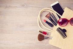 Bolso de la mujer con los objetos del maquillaje y de la moda Visión desde arriba Imagen de archivo