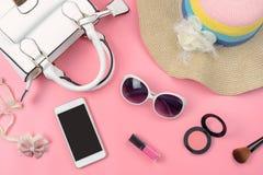 Bolso de la mujer con maquillaje y accesorios aislados en backg rosado Imagenes de archivo