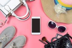 Bolso de la mujer con maquillaje y accesorios aislados en backg rosado Imágenes de archivo libres de regalías